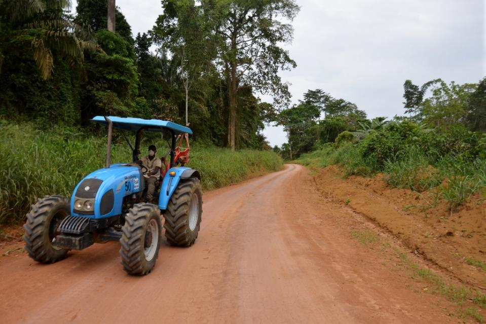 Rubber plantation worker rides a tractor along a jungle road, in Batouri (Photo/AFP/Patrick Fort)