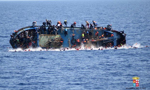 An overcrowded boat of refugees capsizes off the Libyan coast. (Photo/AP)