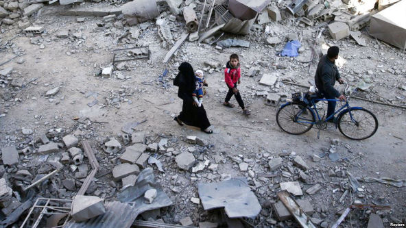 People walk on the rubble of damaged buildings at a site hit yesterday by airstrikes in the rebel held Douma neighborhood of Damascus, Syria, November 18, 2016. (Reuters)