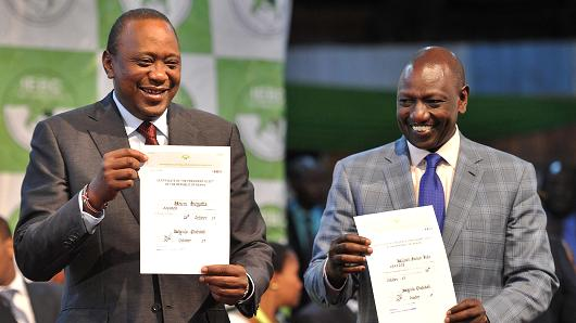 Kenya's president elect, Uhuru Kenyatta (L) with his running mate William Ruto hold up certificates of election October 30, 2017 at the national tallying centre  where they were announced winners of a repeat presidential poll by the Independent Electoral and Boundaries Commission chairman. (AFP/Tony Karumba)