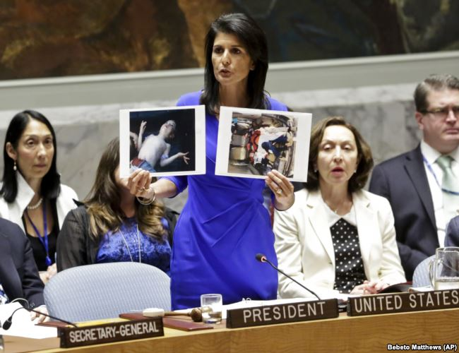 Nikki Haley, United States' Ambassador United Nations, shows pictures of Syrian victims of chemical attacks as she addresses a meeting of the Security Council on Syria at U.N. headquarters in New York, April 5, 2017. (AP/Bebeto Matthews)