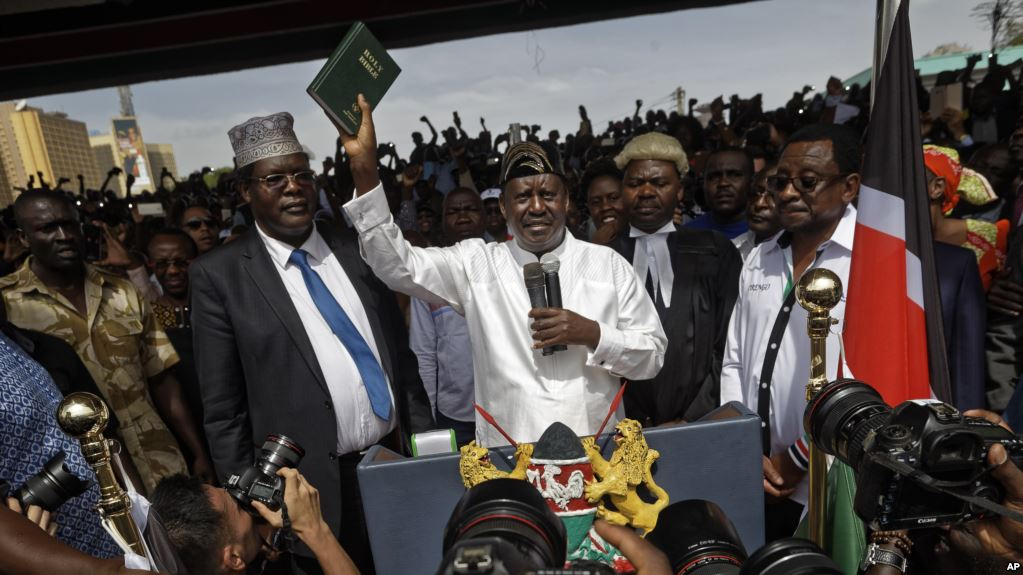 Kenya Opposition leader Raila Odinga holds a bible aloft after swearing an oath during a mock