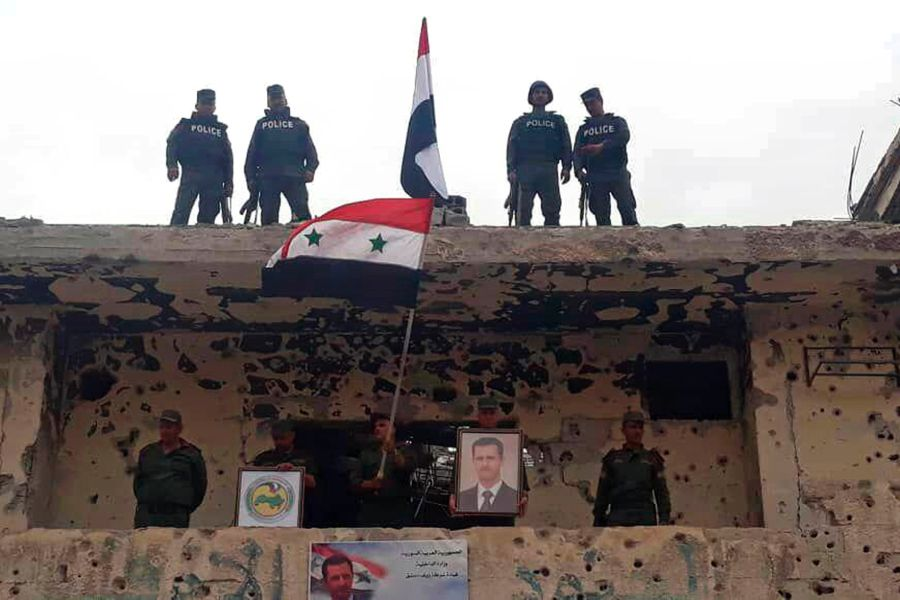 Syrian military and police forces fly their national flags on a damaged building and hold a picture of Syrian President Bashar Assad,  Damascus, Syria. (AP)