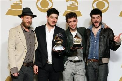 Members of the musical group Mumford & Sons, from left, Ted Dwane, Marcus Mumford, Ben Lovett and Winston Marshall, pose backstage with the best long form music video award for