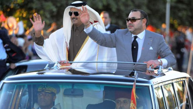 In this photo provided by the Moroccan News Agency, Moroccan King Mohammed VI, right, and The Emir of Qatar, Sheikh Tamim bin Hamad Al-Thani, wave as they stand in an open limousine in Marrakech, Southern Morocco,  December 27, 2013 (AP/MAP, Moroccan Royal Palace)