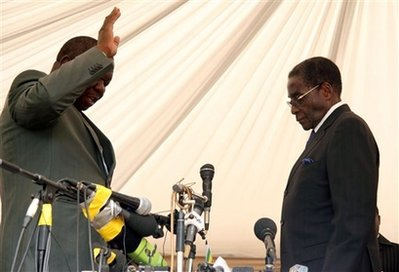 Morgan Tsvangirai, left, leader of the main opposition party in Zimbabwe takes the oath of Prime Minster, in front of President Robert Mugabe, right, at the State House in Harare, Zimbabwe, Wednesday, Feb. 11, 2009.  (AP Photo)