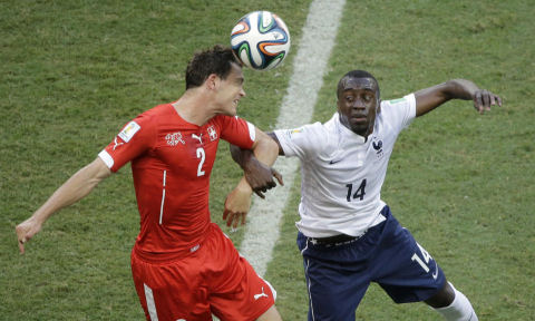 Switzerland's Stephan Lichtsteiner, left, and France's Blaise Matuidi go for a header during the group E World Cup soccer match at the Arena Fonte Nova in Salvador, Brazil, June 20, 2014. (AP/Sergei Grits)