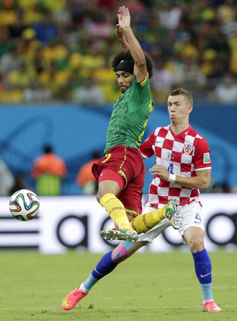 Cameroon's Benoit Assou-Ekotto, left, kicks the ball away from Croatia's Ivan Perisic during the match between Cameroon and Croatia at the Arena da Amazonia in Manaus, Brazil, June 18, 2014. (AP/Marcio Jose Sanchez)