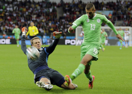 Germany's goalkeeper Manuel Neuer, left, slides in to make a save against Algeria's Islam Slimani during the World Cup 2014 Porto Alegre, Brazil, June 30, 2014. (AP/Matthias Schrader)