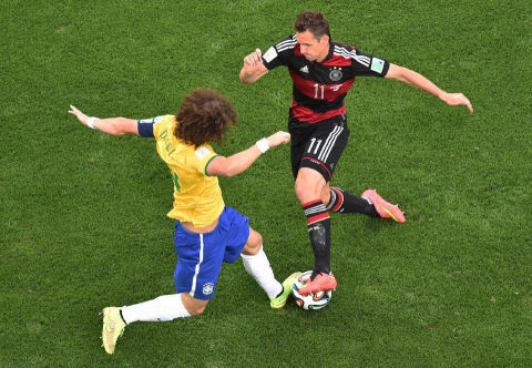 Germany's Miroslav Klose, right, takes on Brazil's David Luiz during the World Cup semifinal soccer match between Brazil and Germany  Brazil, July 8, 2014. (AP/Francois Xavier Marit)