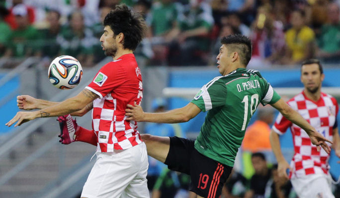 Croatia's Vedran Corluka, left, shields the ball from Mexico's Oribe Peralta  World Cup soccer match between Croatia and Mexico, Brazil, Monday, June 23, 2014. (AP/Sergei Grits)